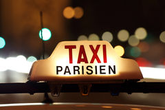 Paris taxi by the Arc de Triomphe. Parisian taxi, with the Arc de Triomphe and traffic light trails in the background Royalty Free Stock Photos