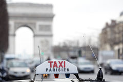 Paris taxi by the Arc de Triomphe. Parisian taxi on avenue des champs-elysees, with the Arc de Triomphe and traffic in the background Royalty Free Stock Photo