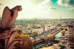 Paris Tilt Shift. Tilt-shift miniature effect of panoramic view across Paris with gargoyle in foreground Royalty Free Stock Images