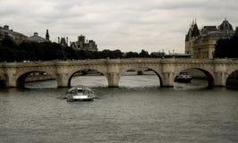 Paris Tour boats under Bridge on River Seine. Tour boats on the River Seine view the city in soft pastel colors under cloudy skies Stock Photography