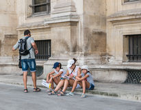 Paris tourist family sits on sidewalk studying maps Stock Photo