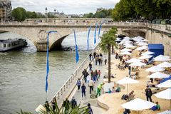 Paris, turistas que relaxam sob os guarda-chuvas de praia france fotografia de stock