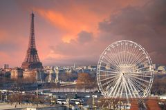 Paris under a thunder-charged sky. Eiffel tower and big wheel, separated by the Seine river and Alexandre Bridge Stock Photo