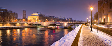 Paris in winter. A quayside (Quai de l'Horloge) along River Seine in Paris covered with snow on a very cold night Stock Image