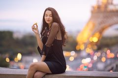 Paris woman smiling eating the french pastry macaron in Paris against Eiffel tower. Paris woman smiling eating the french pastry macaron in Paris. Evening Stock Image