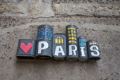 Paris written and painted on tin cans on a wall of Paris, France. stock photography