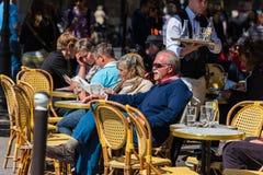 Parisare och turister tycker om mat och drinkar i kafé Royaltyfri Foto