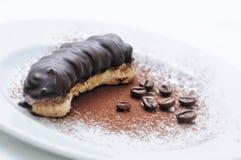 Pariser Kuchen, Schokoladenkuchen auf weißer Platte, Kaffeebohnen, on-line-Shopphotographie, Konditorei, Süßspeise, Kakaopulver Stockfotografie