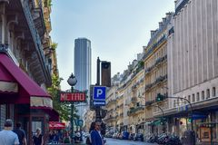 Pariser Straße mit Metro-Zeichen und Montparnasse-Turm im Sommer stockfotografie