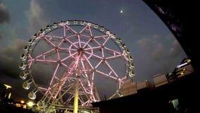 Pariserhjul i rörelse på nöjesfältet på natten stock video