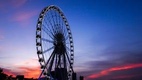 Pariserhjul i rörelse på solnedgångtid Arkivfoto