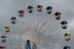 Pariserhjul med färgrika bås i nöjesfältet på bakgrunden av den stormiga himlen royaltyfri fotografi