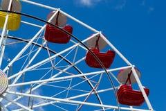 Pariserhjul med gula och röda bunkar mot blå himmel med tunna moln Arkivfoton