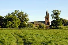 Parish Church. Rural parish church framed between old oak trees at the end of a footpath through a field Stock Image