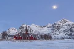 The parish church in Flakstad in the snowy mountains of Lofoten,. The parish church in Flakstad, a red wooden chapel from 1870  between snowy mountains of Stock Images