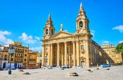 The Parish Church of Floriana, Malta. The ancient Il-Fosos area Granaries in front of magnificent St Publius Church with Neoclassical portico and tall bell Stock Photos