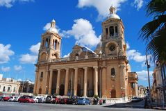 Parish church in Paola, Malta. Paola, Malta – October 1, 2013. Parish church in Paola, Malta with people and cars parked in front of the church and side alley Royalty Free Stock Photos
