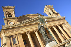 The Parish Church of Santa Maria in Mosta, Malta. Rotated view of the Parish Church of Santa Maria in Mosta, Malta with bronze statue of Virgin Mary and street Stock Photography