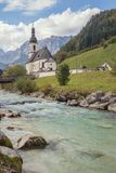 Parish church St. Sebastian seen next to the river. With the Reiter Alpe in background Stock Photos