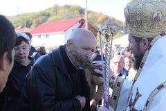 Parishioner kissing the cross. Orthodox parishioner kissing the cross that the priest is holding outside the church in Ramnicu-Valcea city, Romania Royalty Free Stock Photo