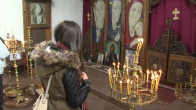 Parishioners, candles, iconostasis in the church of St. Petka in Rupite, Bulgaria stock video