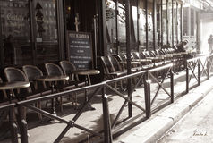 Parisian Cafe. Seats arranged facing the streets, lined outside a cafe in the streets of Paris with a couple seated at the end and a pedestrian walking away in royalty free stock photos