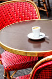 Parisian cafe terrace with red chairs and an espresso Royalty Free Stock Image