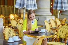 Parisian girl in an outdoor cafe using tablet Stock Photos