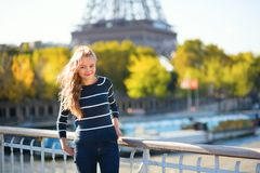Parisian girl walking near the Eiffel tower Royalty Free Stock Photos