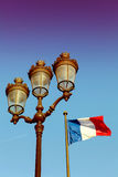 Parisian Lantern and French Flag. Typical lantern of Paris and French flag waving in the wind in front of a blue sky stock image