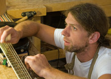 Parisian Luthier Repairing Guitar. This shot was taken in a guitar repair shop in Paris, France Stock Photos