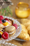 Parisian macarons, raspberries and other delicacy Royalty Free Stock Photography