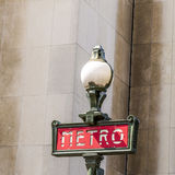 Parisian metro sign with a lamppost against  vintage wall Stock Photo