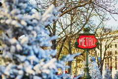 Parisian metro sign with trees covered with snow Royalty Free Stock Photography