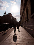 Parisian street. Contre jour shot of a street in Paris with a sillhouette riding a bike in the foreground Stock Images