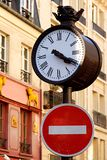 Parisian street clock. And traffic sign - Paris, France royalty free stock image