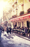 Parisian street scene. Street in paris with cafe and parisians enjoying the sunny day Royalty Free Stock Image