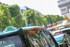 Parisian taxi on avenue des champs-elysees, with the Arc de Trio. Mphe and traffic in the background Royalty Free Stock Photography