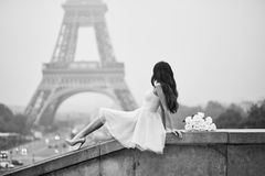 Parisian woman in front of the Eiffel tower. Elegant Parisian woman in pink tutu dress with white roses sitting near the Eiffel tower at Trocadero view point in Royalty Free Stock Photo