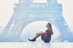Parisian woman near the Eiffel tower at morning. Beautiful elegant Parisian woman near the Eiffel tower at early morning Royalty Free Stock Image