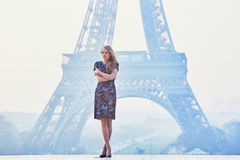 Parisian woman near the Eiffel tower at morning Stock Photos