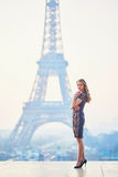Parisian woman near the Eiffel tower at morning Royalty Free Stock Photography