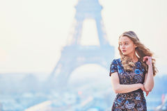 Parisian woman near the Eiffel tower at morning Royalty Free Stock Photos