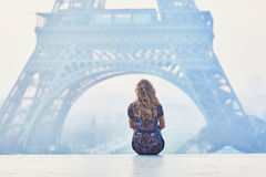 Parisian woman near the Eiffel tower at morning. Beautiful elegant Parisian woman near the Eiffel tower at early morning Stock Photos