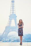 Parisian woman near the Eiffel tower at morning. Beautiful elegant Parisian woman near the Eiffel tower at early morning Royalty Free Stock Photo