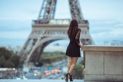 Parisian woman near the Eiffel tower in Paris, France. Elegant romantic Parisian woman in black sexy dress with flowers standing near the Eiffel tower at Stock Images