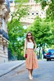 Parisian woman near the Eiffel tower on a summer day Royalty Free Stock Image