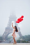 Parisian woman with red balloons in front of the Eiffel tower. Happy young woman in pink tutu dress with bunch of red balloons near the Eiffel tower in Paris Stock Image