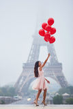 Parisian woman with red balloons in front of the Eiffel tower. Happy young woman in pink tutu dress with bunch of red balloons near the Eiffel tower in Paris Stock Images