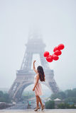 Parisian woman with red balloons in front of the Eiffel tower. Happy young woman in pink tutu dress with bunch of red balloons near the Eiffel tower in Paris Royalty Free Stock Image